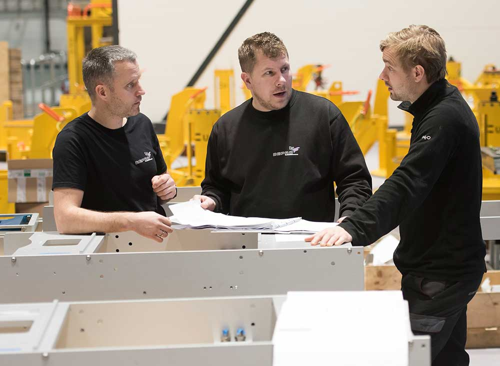 Three men discussing solutions in Depro's workshop.