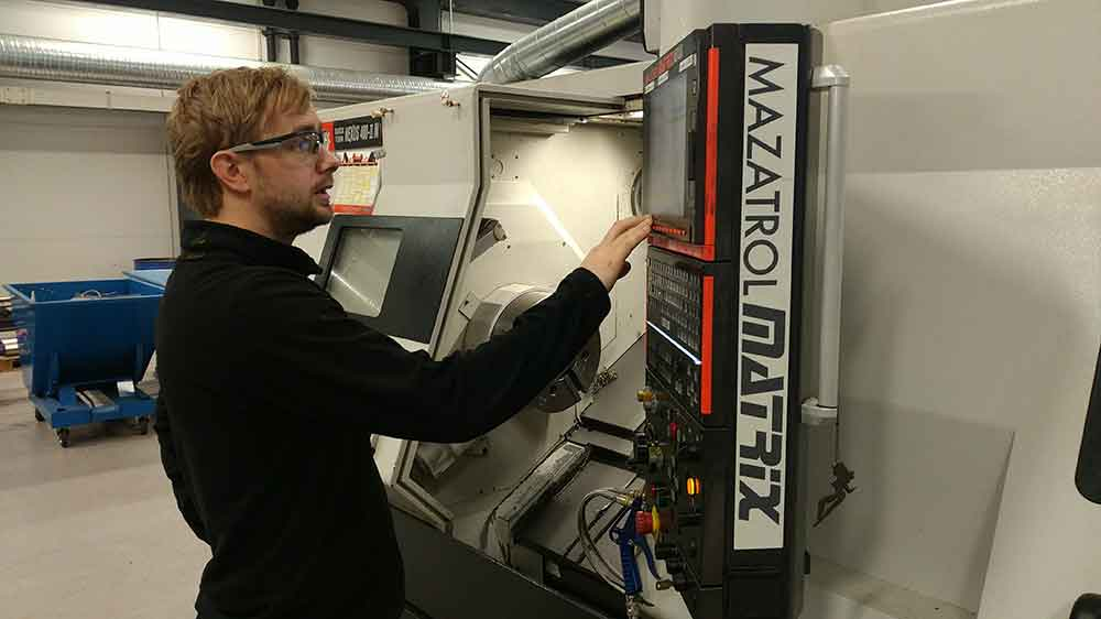 Male employee at Depro AS works at a CNC machine.