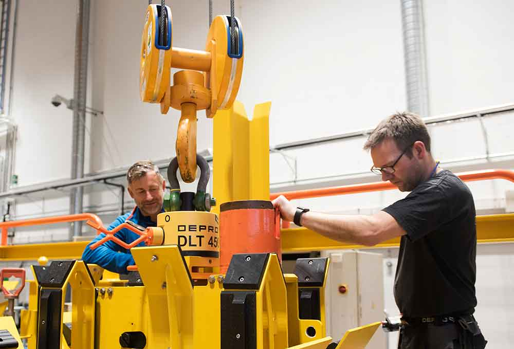 Two male employees at Depro AS work in the workshop with subsea equipment.