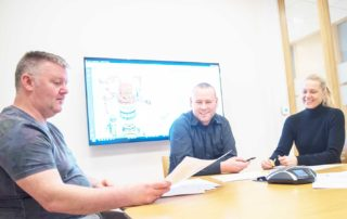 Two men and a woman sit in a meeting room in the Depro building and look at the drawings of a new product