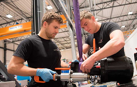 Two men working on a subsea torque tool in depro's workshop